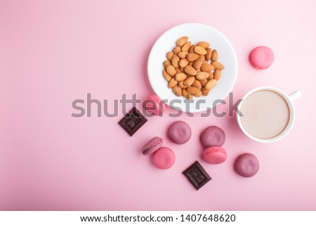 Purple and pink macaron or macaroon cakes with cup of coffee and almonds on pastel pink background. Morninig, spring, fashion composition. Flat lay, top view, copy space.