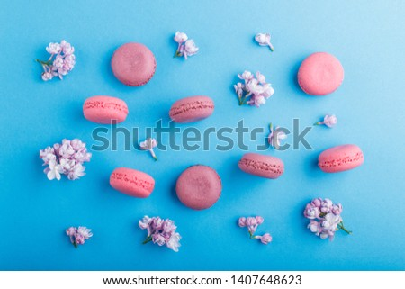 Purple and pink macaron or macaroon cakes with lilac flowers on pastel blue background. Morninig, spring, fashion composition. Flat lay, top view, pattern.