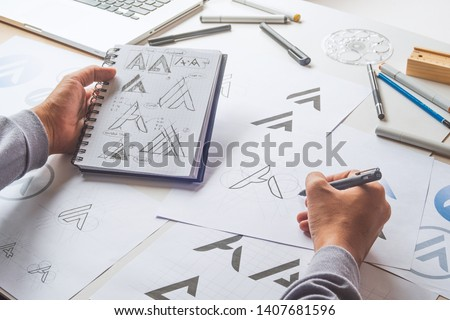 Graphic designer drawing sketch design creative Ideas draft Logo product trademark label brand artwork. Graphic designer studio Concept. #1407681596