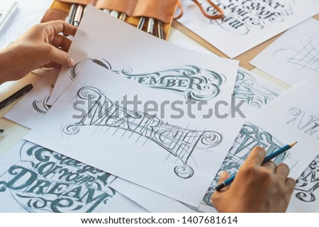 Typography Calligraphy artist designer drawing sketch writes letting spelled pen brush ink paper table artwork.Workplace design studio. #1407681614