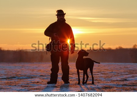 A hunter in the hat with a gun and his German Shorthaired Pointer dog breed friend. Beautiful silhouettes on the background of the dawn. Amazing winter morning. #1407682094