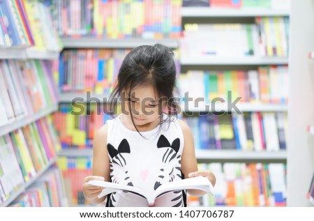 Asian child reading or kid girl happy smile and shopping or choose knowledge or text book on bookshelf in bookstore or library room at kindergarten school or nursery for learn and study with education #1407706787