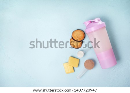 shake with protein drink, protein powder, protein bars and protein cookies on a blue background. view from above. copy space #1407720947