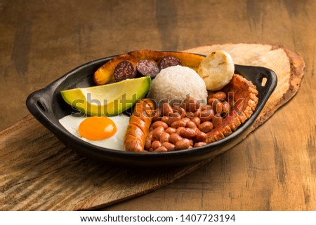 Bandeja paisa, typical dish at the Antioqueña region of Colombia. It consists of chicharrón (fried pork belly), black pudding, sausage, arepa, beans, fried plantain, avocado egg, and rice #1407723194