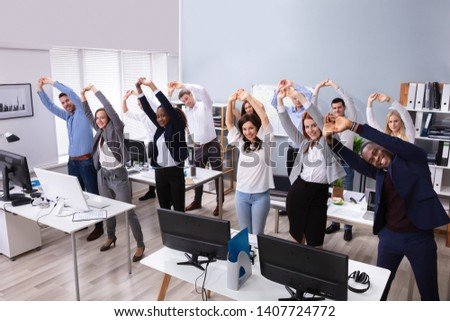 Group Of Smiling Multi-ethnic Businesspeople Doing Stretching Exercise At Workplace #1407724772