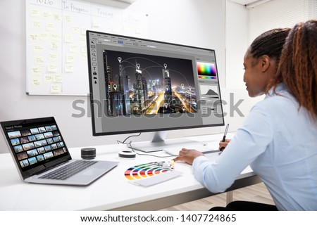 Young Female Designer Editing Photos On Computer In Office