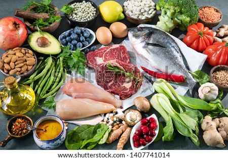 Balanced diet food background. Selection of various paleo diet products for healthy nutrition. Superfoods, meat, fish, legumes, nuts, seeds, greens and vegetables #1407741014
