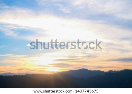 Mountain panorama from a bird's eye view. The sky above the mountain peaks at sunset. Bright multi-colored clouds, the sun's rays pass through the air and make orange, yellow, pink reflexes #1407743675