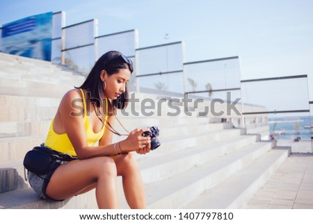 Skilled female amateur photographer checking photos on vintage camera spending time for images hobby, Latin hipster girl resting on urban setting and editing pictures on old fashioned technology