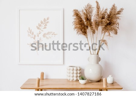 Stylish korean interior of living room with white mock up poster frame, elegant accessories, air plant, wooden shelf and vase with flowers. Minimalistic concept of home decor. Template. Bright room. Royalty-Free Stock Photo #1407827186