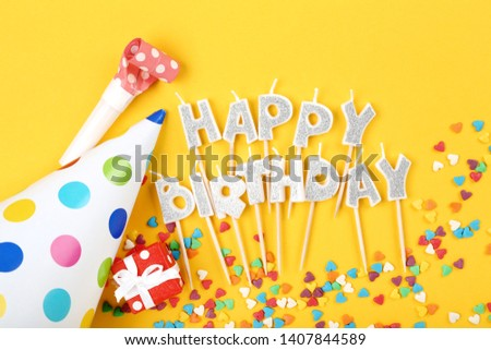 Happy Birthday candles with party decorations and sprinkles on yellow background