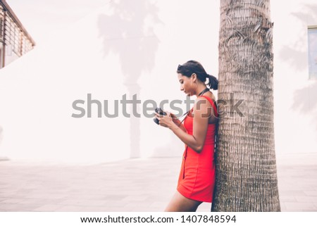 Side view of Spanish hipster girl standing near summer tree and editing photos made during journey trip, attractive Latin woman checking settings on old fashioned camera for favourite hobby