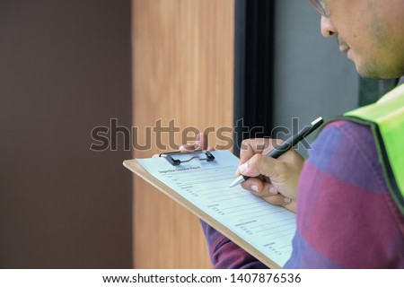 Worker, Inspector or engineer is checking and inspecting the building or house by using checklist #1407876536