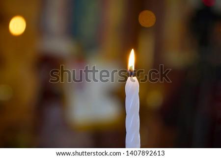 Burning white candle on blurred dark background #1407892613