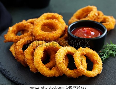 Homemade crunchy fried onion rings with tomato sauce  Royalty-Free Stock Photo #1407934925