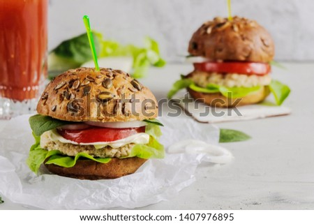 Vegetarian hamburger with tomato, lettuce, onion, bean cutlet and grain bun is an alternative to the usual hamburger. Next to a glass of fresh tomato juice. The concept of healthy eating. #1407976895