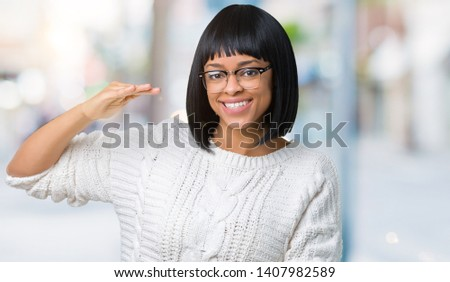 Beautiful young african american woman wearing glasses over isolated background gesturing with hands showing big and large size sign, measure symbol. Smiling looking at the camera. Measuring concept. #1407982589