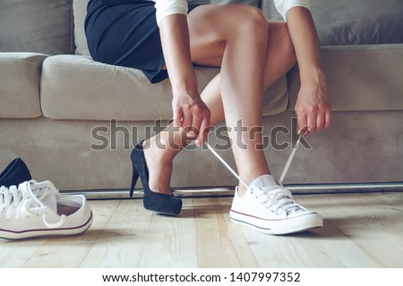Young beautiful woman makes the choice between comfortable and uncomfortable shoes. Beautiful or comfortable shoes concept #1407997352