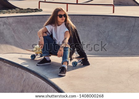Trendy young woman with long hair and sunglasses is sitting at skatepark on her longboard. #1408000268
