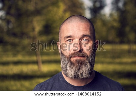 A white man about 43 years old with short hair and beard has a rest in a park, close-up. Royalty-Free Stock Photo #1408014152
