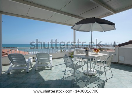 Italy, Sicily, Marina di Ragusa (Ragusa Province); elegant private apartment, view of the terrace with the dining table and the sea #1408016900