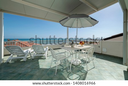 Italy, Sicily, Marina di Ragusa (Ragusa Province); elegant private apartment, view of the terrace with the dining table and the sea #1408016966