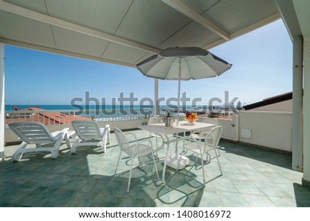 Italy, Sicily, Marina di Ragusa (Ragusa Province); elegant private apartment, view of the terrace with the dining table and the sea #1408016972