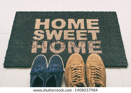 Door mat Shoes at front entrance of condo apartment. Written welcome sign Home Sweet Home welcoming homeowners at new house moving in couple's pairs of sneakers lying on the floor. #1408037984