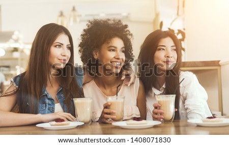 Three smiling multiracial girls sitting in cafe looking aside, drinking coffee and having enjoyable time #1408071830