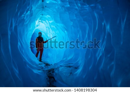 Man inside a melting glacier ice cave. Cut by water from the warming, melting glacier, the cave runs deep into the ice of the Matanuska Glacier in Alaska. #1408198304