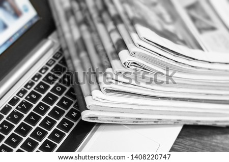 Newspapers and laptop. Pile of daily papers with news on the computer. Pages with headlines, articles folded and stacked on keypad of electronic device. Modern gadget and old journals, focus on paper  #1408220747
