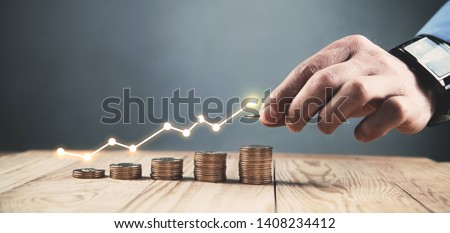 Man stacking coins with a graph of profit. #1408234412