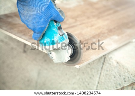 Worker cutting a tile with a grinder. #1408234574