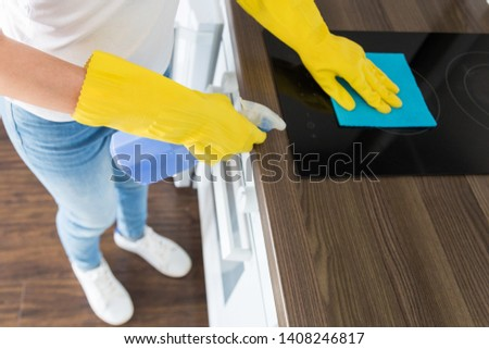 A young woman from a professional cleaning company cleans up at home. A man washes the kitchen in yellow gloves with cleaning supplies stuff. #1408246817