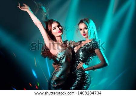Fashion models sexy women dancing on disco party in neon light, night club dancers, beautiful model girls, Art design. Disco dancers posing in UV, colorful lights. Holiday Make up. Colorful background