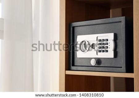 Small modern safe on shelf Royalty-Free Stock Photo #1408310810