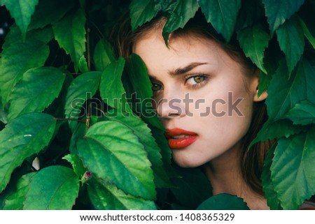 green leaves of bushes, woman bright makeup red lipstick shadows beautiful face close-up                   #1408365329