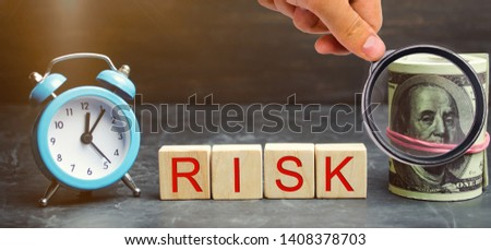 Money, clock and wooden blocks with the word Risk. The concept of financial risk. Justified risks. Investing in a business project. Making the right decision. Property insurance. Legal / market risks #1408378703