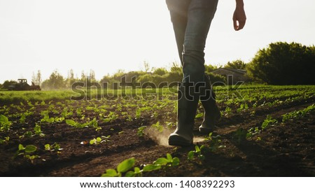 A farmer walks across a field in rubber boots on a blurred background of the tractor in motion. Concept of: Rubber boots, Lifestyle, Farmer, Slow Motion, Fields. #1408392293