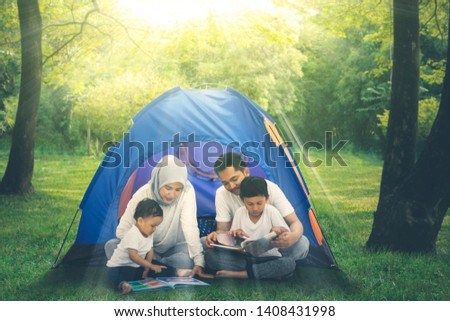 Picture of Muslim family reading books in a tent while camping in the forest at morning time