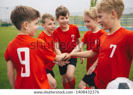 Happy boys play team sport. Kids smiling in school sports team. Junior sports teamwork; kids put hands together. Cheerful children boys players of school soccer team. Happy boys in youth football team #1408432376