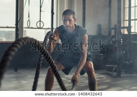 Strong young man working out with battle ropes in a crossfit gym. Muscular sportsman doing cross excursion with ropes in workout gym. Determined guy using battle rope while doing physical training. #1408432643