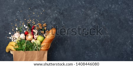 Paper bag vegetables and fruit on a dark background with copy space top view. Bag food concept Royalty-Free Stock Photo #1408446080