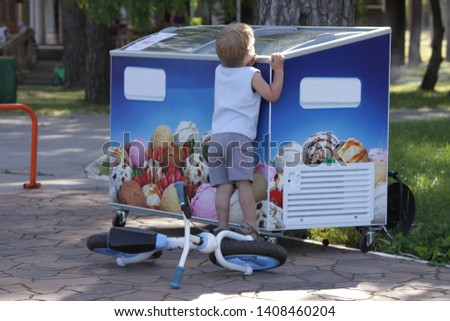 Child and ice cream. small child with a bicycle looks in the kiosk with ice cream. Summer ice cream. Kiosk with ice cream.