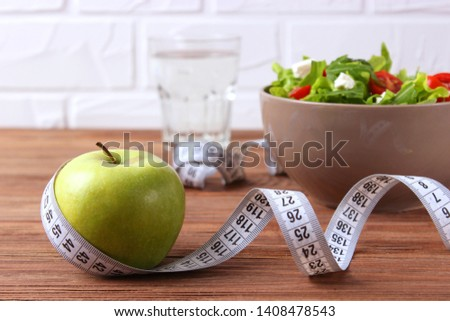 tape and lettuce on a light background. Slimming, diet, healthy food.  #1408478543