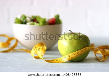 tape and lettuce on a light background. Slimming, diet, healthy food.  #1408478558