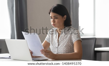 Stressed upset asian business woman student worker reading bad news in paper letter report feel frustrated about debt notification rejection failed test exam result sitting at office desk, got fired #1408495370