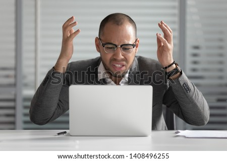 Angry stressed african business man using laptop mad about broken computer online problem annoyed with slow stuck laptop error, crazy about system virus or data loss, outraged with website mistake #1408496255