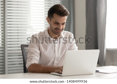 Smiling male entrepreneur working on computer sit at office desk, happy businessman professional typing corporate email using laptop communicating online using software for business at workplace #1408499936