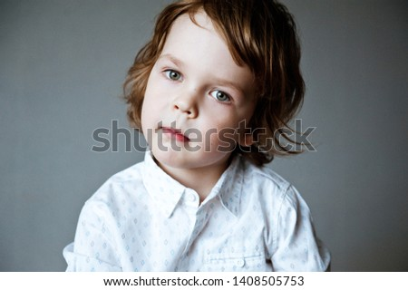 Portrait of cute boy in white shirt on grey background. #1408505753